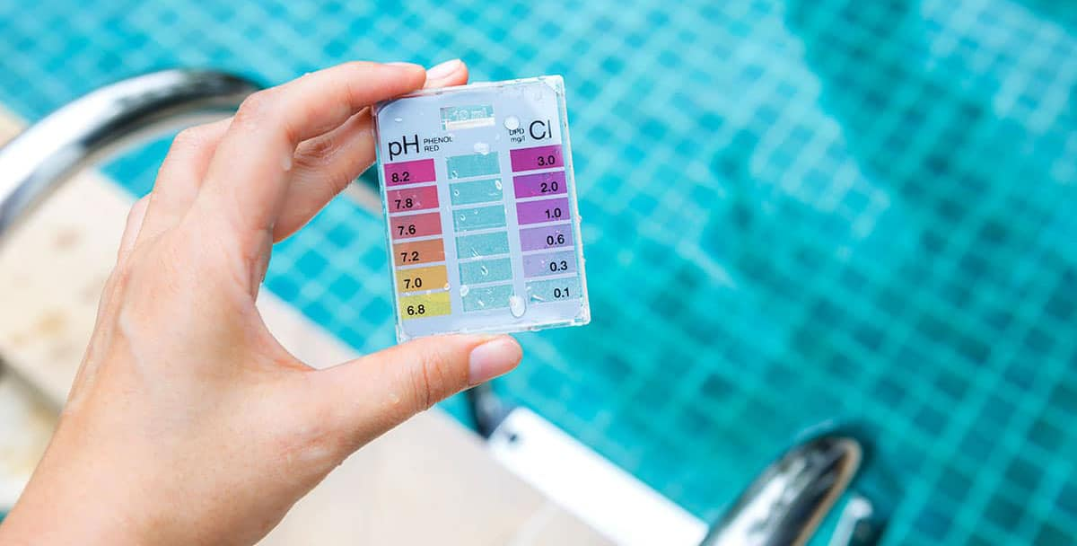 person holding a pH and chlorine test in front of a pool