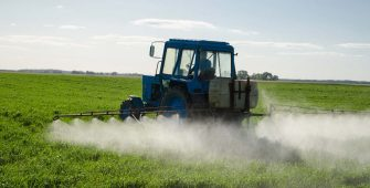 tractor spraying agricultural field